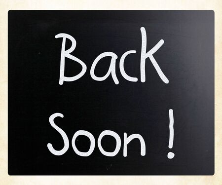 'Back soon!' handwritten with white chalk on a blackboard photo