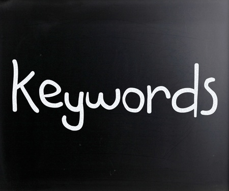 The word 'Keywords' handwritten with white chalk on a blackboard photo