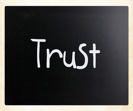 The word Trust handwritten with white chalk on a blackboard photo
