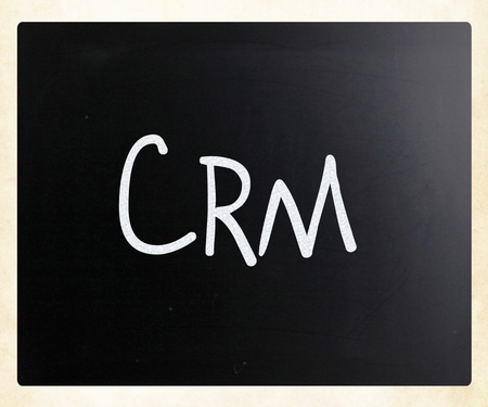 The word 'CRM' handwritten with white chalk on a blackboard photo
