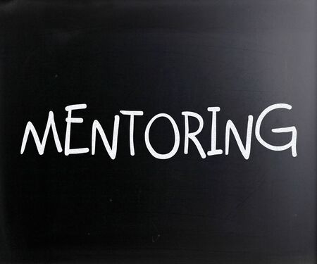 The word Mentoring handwritten with white chalk on a blackboard photo