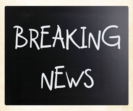 Breaking news handwritten with white chalk on a blackboard photo