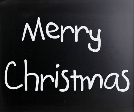 'Merry Christmas' handwritten with white chalk on a blackboard photo