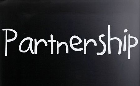The word 'Partnership' handwritten with white chalk on a blackboard photo