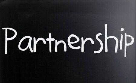 The word Partnership handwritten with white chalk on a blackboard photo