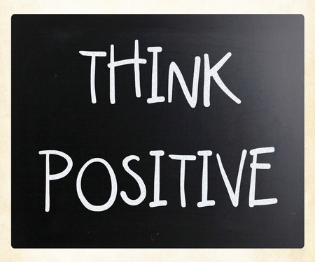 Think positive handwritten with white chalk on a blackboard photo