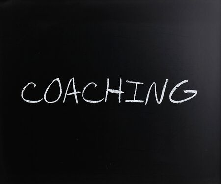 Coaching, handwritten with white chalk on a blackboard. photo