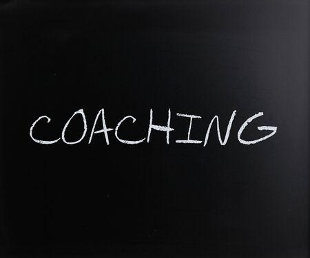 Coaching, handwritten with white chalk on a blackboard. Stock Photo - 13313438