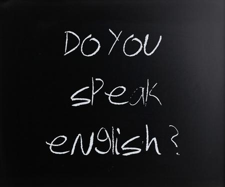 Do you speak english, handwritten with white chalk on a blackboard. photo