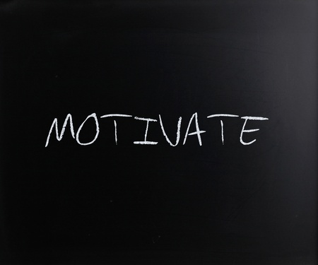 Motivate, handwritten with white chalk on a blackboard. photo
