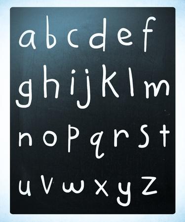 prinitng block: Complete english alphabet handwritten with white chalk on a blackboard
