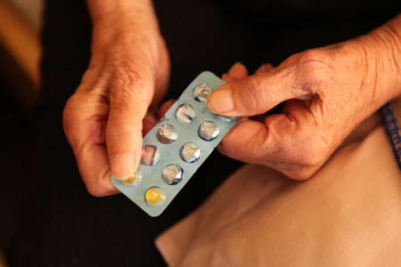 Close up of old hands with tablets. Stock Photo - 13852492