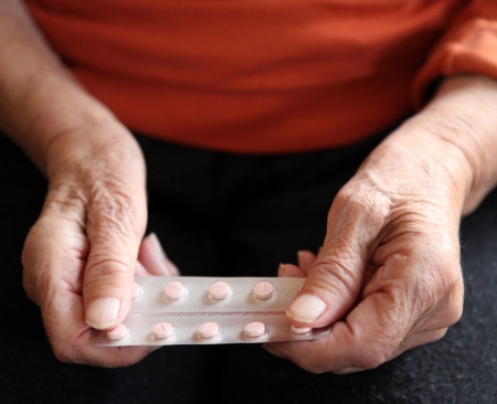Close up of old hands with tablets.