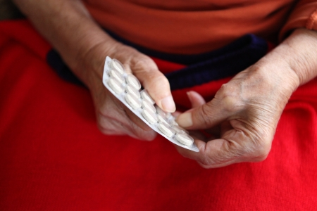 abatement: Close up of old hands with tablets.