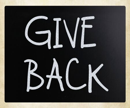 Give back handwritten with white chalk on a blackboard. Stock Photo