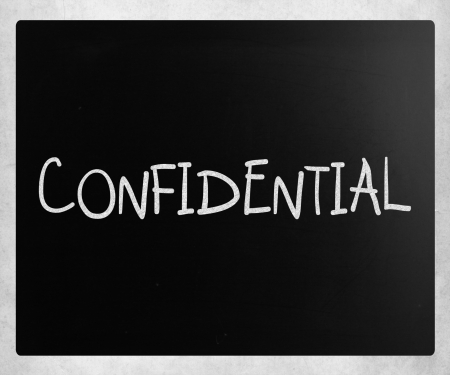 The word Confidential handwritten with white chalk on a blackboard photo