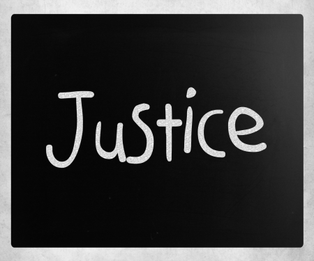 The word Justice handwritten with white chalk on a blackboard photo