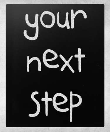 Your next step handwritten with white chalk on a blackboard photo