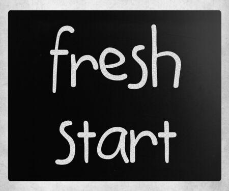 """frisse start: """"Nieuwe start"""" met de hand geschreven met wit krijt op een schoolbord"""