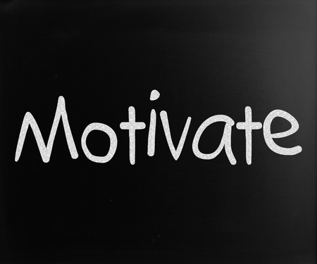 Motivate handwritten with white chalk on a blackboard Stock Photo