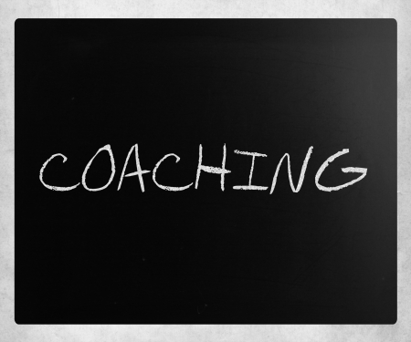 Coaching handwritten with white chalk on a blackboard. photo