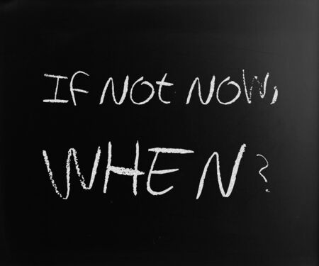 If not now, when? handwritten with white chalk on a blackboard. photo