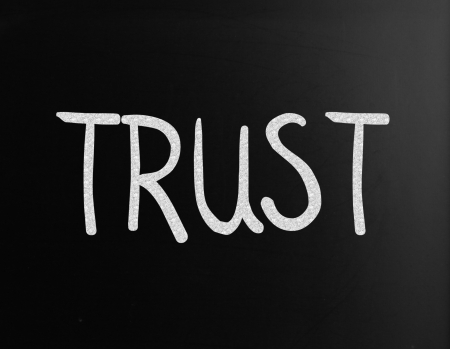 The word Trust handwritten with white chalk on a blackboard Stock Photo