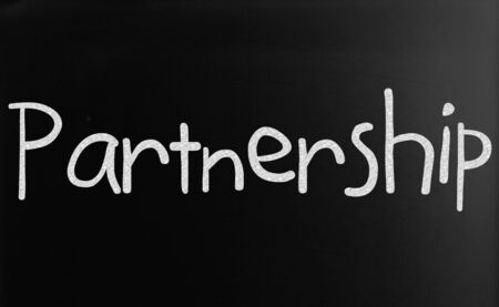 The word Partnership handwritten with white chalk on a blackboard photo