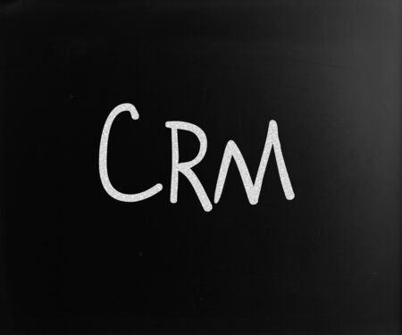 The word CRM handwritten with white chalk on a blackboard photo