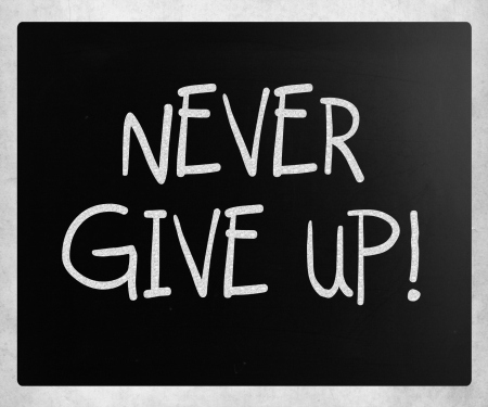 Never give up handwritten with white chalk on a blackboard photo