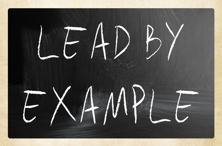 Lead by example handwritten with white chalk on a blackboard. photo