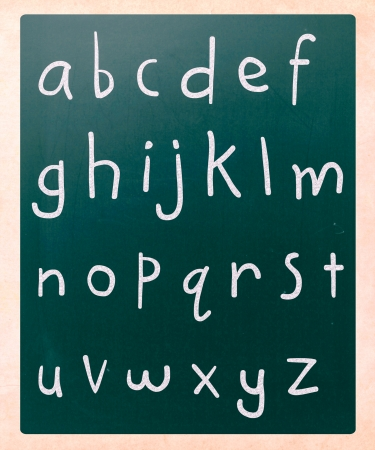 Complete english alphabet handwritten with white chalk on a blackboard photo
