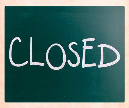 The word Closed handwritten with white chalk on a blackboard photo