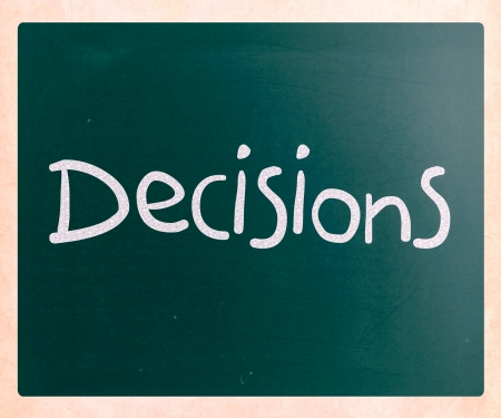The word Decisions handwritten with white chalk on a blackboard photo