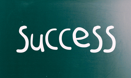 The word Success handwritten with white chalk on a blackboard photo