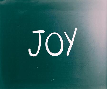The word Joy handwritten with white chalk on a blackboard photo