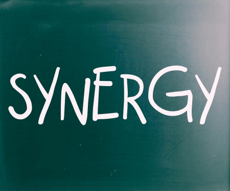 combined effort: The word Synergy handwritten with white chalk on a blackboard Stock Photo