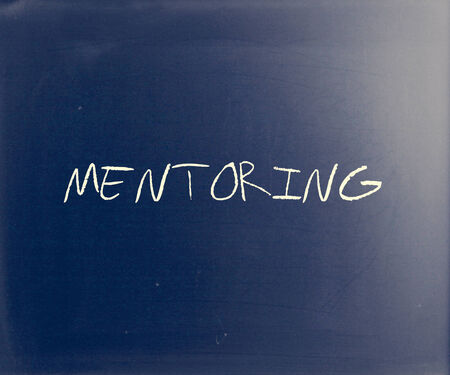 perceived: The word Mentoring handwritten with white chalk on a blackboard. Stock Photo