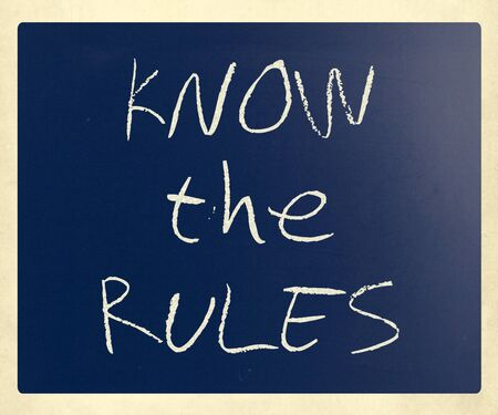 Know the rules handwritten with white chalk on a blackboard. photo