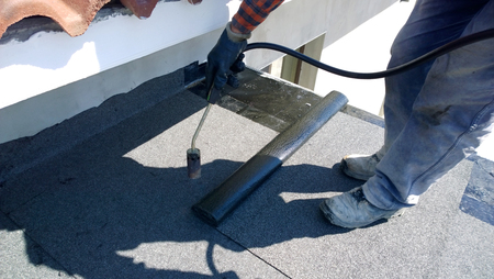 ruberoid: Roofer preparing part of bitumen roofing felt roll for melting by gas heater torch flame