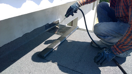 roofing membrane: Roofer preparing part of bitumen roofing felt roll for melting by gas heater torch flame