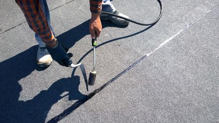 bitumen felt: Roofer preparing part of bitumen roofing felt roll for melting by gas heater torch flame