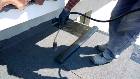 roofing felt: Roofer preparing part of bitumen roofing felt roll for melting by gas heater torch flame
