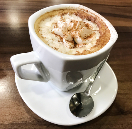Cup of cappuccino served on table