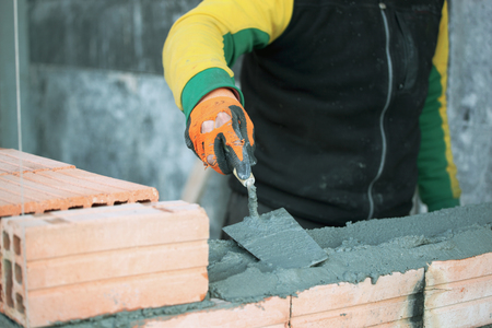 Industrial bricklayer installing bricks on construction site.