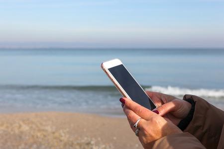 Beautiful Woman Using Smart Phone On A Beach