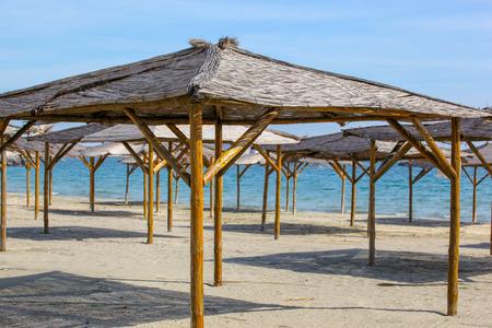 Umbrellas In Sand On Empty Beach