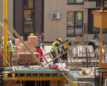 Pomorie, Bulgaria - March 14, 2019: Bricklayer Preparing Laying Bricks On Wall.