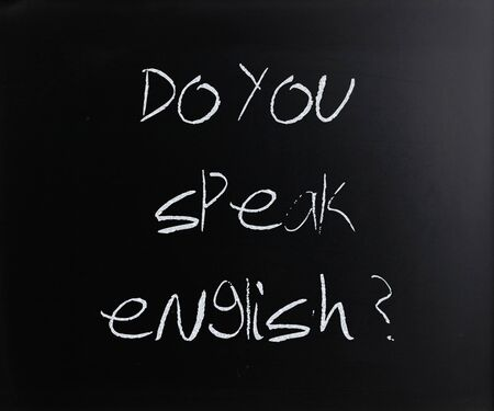 """Do you speak english"" on a blackboard."