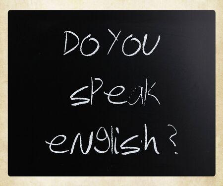 """""""Spreek je Engels"""" handgeschreven met wit krijt op een schoolbord."""